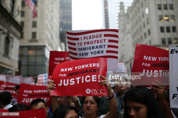 A protester holds a banner reading 'New Yorkers For Immigrant Justice' during a rally against US President Donald J Trump's potential repealing of...