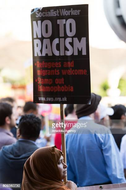 A protester holds a banner reading 'No To Racism Refugees And Migrants Welcome Stamp Out Islamophobia' at a vigil for Resham Khan and Janeel Muhktar...