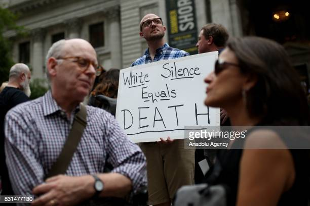 A protester holds a banner reading 'White Silence Equals Death' during a rally against US President Donald J Trump for threating North Korea and...