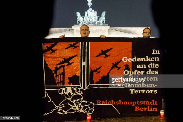 A protester holds a banner with the slogan 'In Gedenken an die Opfer des alliierten Bombenterrors Reichshauptstadt Berlin' while supporters of the...