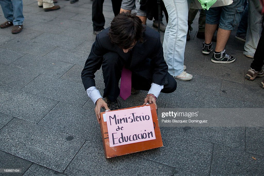 A protester holds a briefcase displaying the sign 'Ministery of Education' during a demonstration by students protesting against education cuts at Puerta del Sol on October 11, 2012 in Madrid, Spain. Ratings agency Standard & Poor's has cut Spain's credit rating down to BBB-. The Spanish government has already introduced spending cuts and tax increses in an attempt to ease the country's debt and reduce high unemployment levels. Spain's Minister of Economy Minister Luis de Guindos maintains that the country will not need to request a bailout.