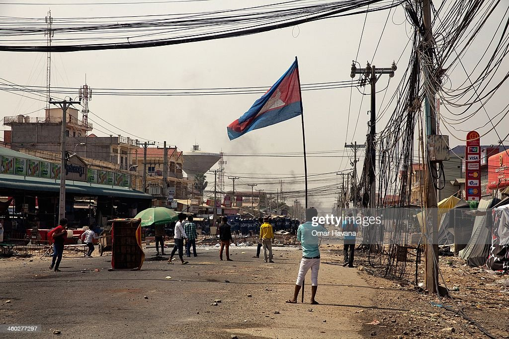 A protester holds a Cambodian National flag during clashes between garment workers and police forces in Veng Sreng Boulevard on January 3, 2014 in Phnom Penh, Cambodia. Several people have been injured, and at least three people have reported dead after police broke up demonstrations on Veng Sreng Boulevard by garment workers demanding wage increases beyond the industry minimum wage set last week by the Ministry of Labour's Labour Committee.