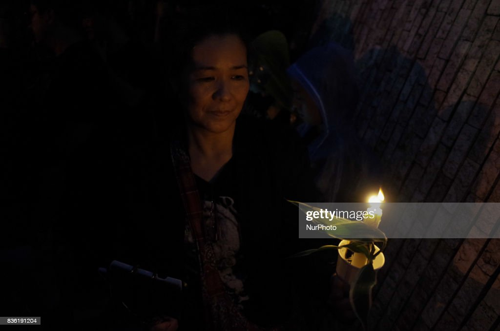 A protester holds a candle during a rally against extrajudicial killings in Quezon City, east of Manila, Philippines on Monday, 21 August 2017. The death of Kian Delos Santos, who was killed by policemen in an alleged shootout, has sparked protests and condemnation from the public against alleged extrajudicial killings on drug users and pushers.