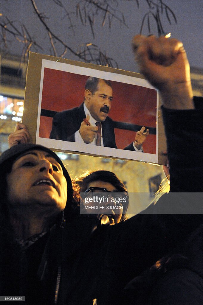 A protester holds a cardboard bearing a portrait of Tunisian opposition leader Chokri Belaid during a demonstration on February 6, 2013 held outside the Tunisian embassy in Paris against his killing today outside his home. Furious protesters on February 6 erected barricades in central Tunis and hurled rocks at police who tried to disperse them with tear gas in new clashes after the assassination of a prominent opposition figure. AFP PHOTO / MEHDI FEDOUACH