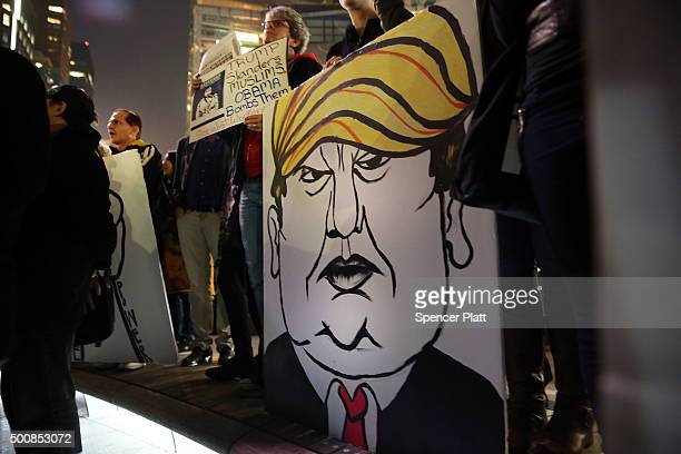 A protester holds a caricature of conservative presidential candidate Donald Trump during a demonstration against racism and Trump's recent remarks...