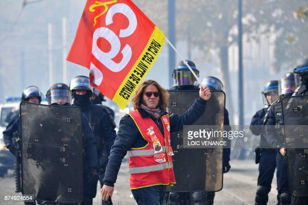 A protester holds a CGT labour union flag in front of French riot police officers during a demonstration as part of a nationwide protest day against...