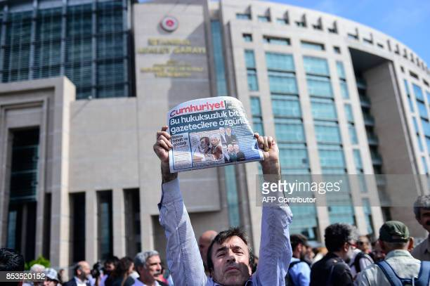 A protester holds a copy of the Cumhuriyet daily during a demonstration in front of Istanbul's courthouse on September 25 2017 during a hearing in...