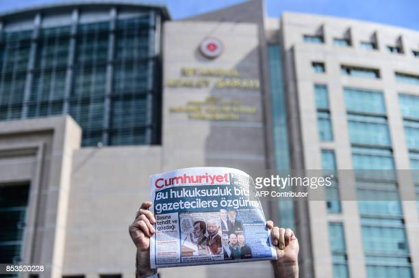 A protester holds a copy of the Cumhuriyet daily during a demonstration in front of Istanbul's court house on September 25 2017 during a hearing in...