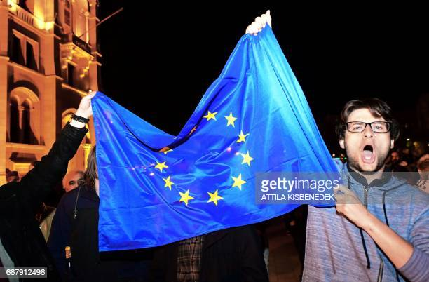 A protester holds a European flag during a demonstration against Hungarian Prime Minister Viktor Orban's government in front of the parliament...