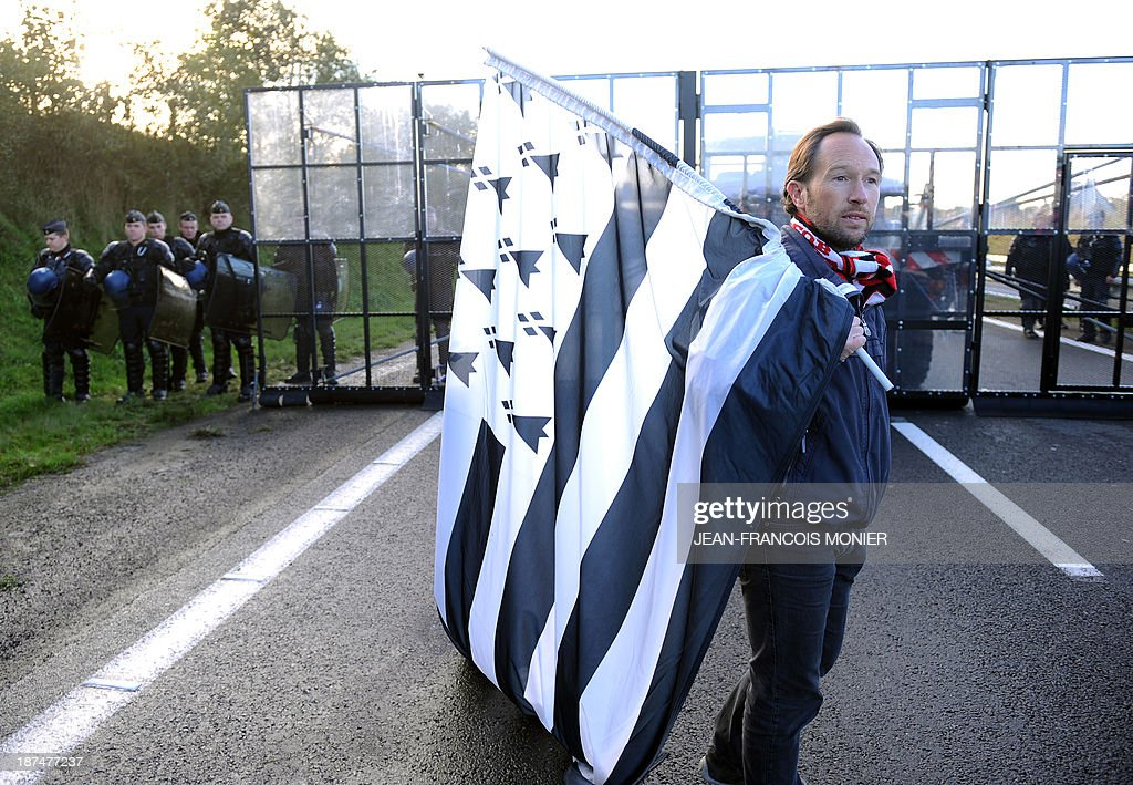 A protester holds a flag of French western region Brittany in front of French riot police protecting an 'Ecotax' control portal during a demonstration against jobcuts and against the government's controversial environmental tax on heavy goods vehicles in Jugon-les-Lacs, western France, on November 9, 2013. The ecotax, aimed at encouraging environmentally friendly commercial transport, imposes new levies on French and foreign vehicles transporting commercial goods weighing over 3.5 tonnes but its implementation has repeatedly been put off. AFP PHOTO / JEAN-FRANCOIS MONIER