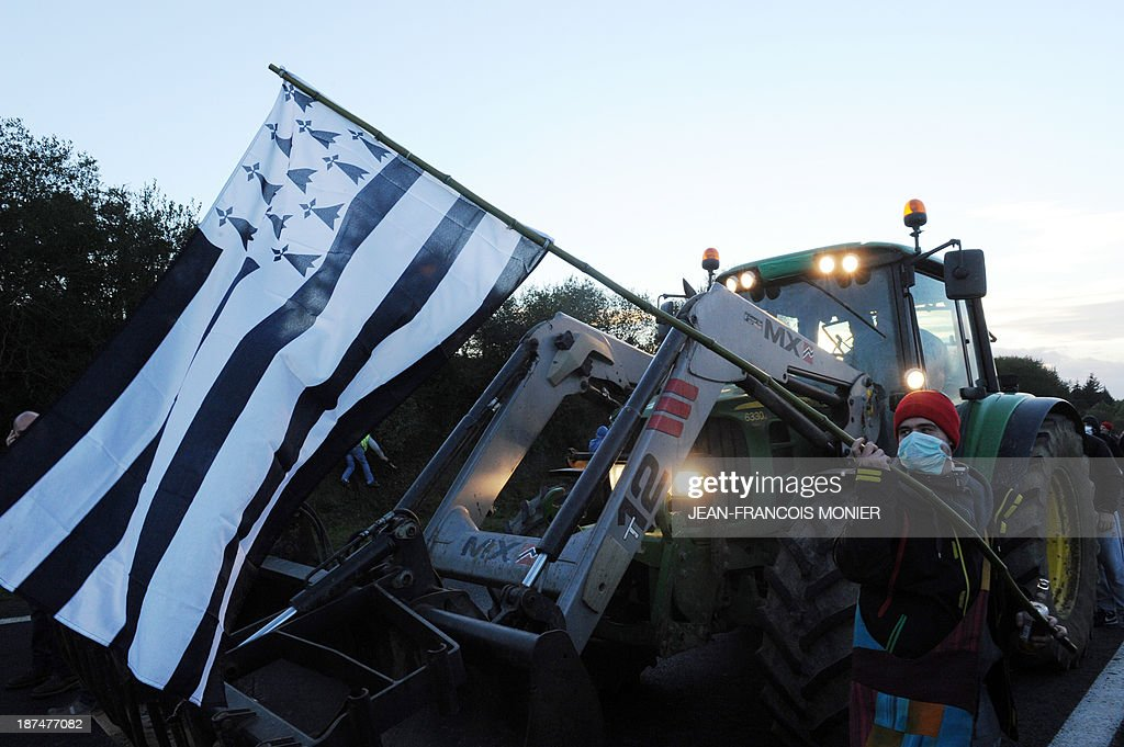 A protester holds a flag of French western region Brittany near a tractor in front of an 'Ecotax' control portal during a demonstration against jobcuts and against the government's controversial environmental tax on heavy goods vehicles in Jugon-les-Lacs, western France, on November 9, 2013. The ecotax, aimed at encouraging environmentally friendly commercial transport, imposes new levies on French and foreign vehicles transporting commercial goods weighing over 3.5 tonnes but its implementation has repeatedly been put off.