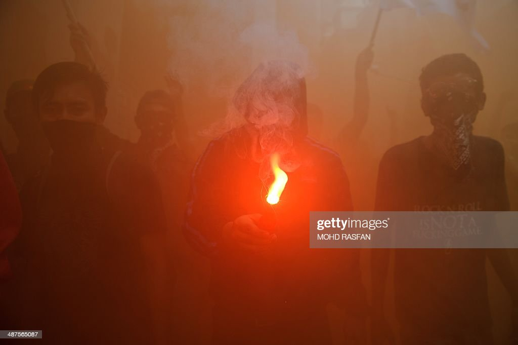A protester holds a flair up in the smoke during a May Day protest in Kuala Lumpur on May 1 2014 Malaysia's opposition and activists demonstrate on...