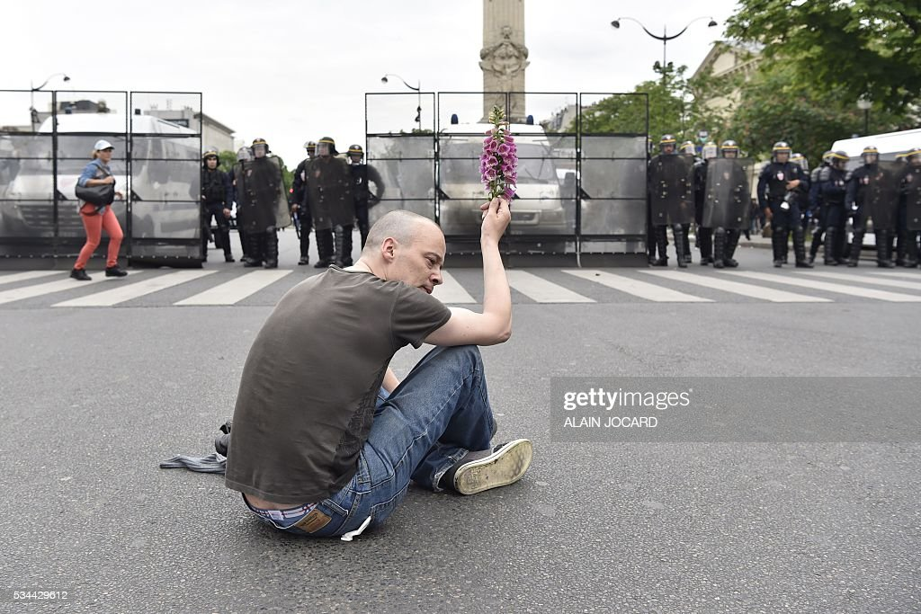 A protester holds a flower in front ot French riot police during a protest against the government's labour market reforms in Paris, on May 26, 2016. The French government's labour market proposals, which are designed to make it easier for companies to hire and fire, have sparked a series of nationwide protests and strikes over the past three months.