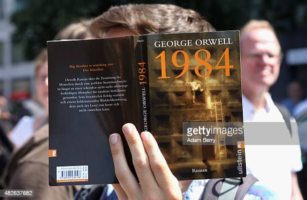 A protester holds a German translation of George Orwell's book '1984' as he demonstrates for journalists' rights on August 1 2015 in Berlin Germany...