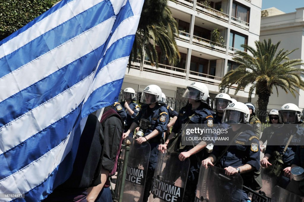 A protester holds a Greek flag in front of the police deployed by the ministry of administrative reform in Athens during a massive protest march by municipal workers and contract workers against the latest law tablet to parliament on April 26, 2013. Greece tabled to parliament a law enshrining the latest reforms agreed with its troika of international creditors earlier this month in return for 8.8 billion euros ($11.4 billion) in bailout loans.The legislation, slated for a vote late on Sunday, formalises the dismissal of 15,000 civil servants by 2014, including 4,000 this year. This includes staff being pensioned off, fired for corruption of incompetence, or made redundant through the elimination of state entities.