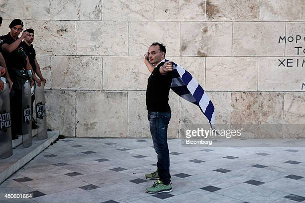 A protester holds a Greek national flag in front of policemen during an antiEuropean Union rally outside the parliament in Athens Greece on Monday...