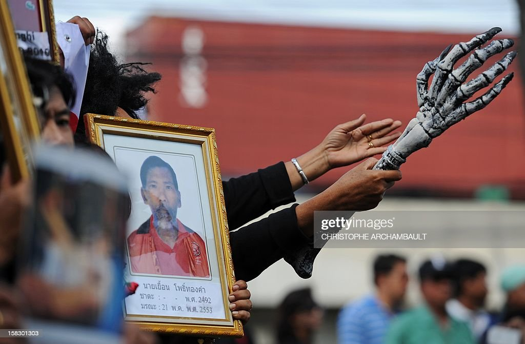 A protester holds a mock skeleton's arm (R) as a symbol of death as others hold pictures of some of those killed during a crackdown on anti-government rallies two years ago as former Thai prime minister Abhisit Vejjajiva (not pictured) appears at a justice ministry building to be charged with murder over a civilian's death during the crackdown, in Bangkok on December 13, 2012. Abhisit, along with his then-deputy Suthep Thaugsuban, were to be charged at the Department of Special Investigation (DSI), making them the first officials to face a court over Thailand's worst political violence in decades. AFP PHOTO/Christophe ARCHAMBAULT