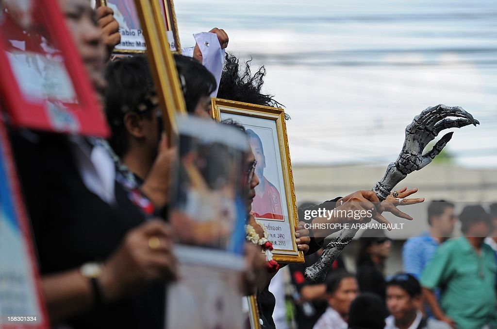 A protester holds a mock skeleton's arm (R) as a symbol of death as others hold pictures of some of those killed during a crackdown on anti-government rallies two years ago as former Thai prime minister Abhisit Vejjajiva (not pictured) appears at a justice ministry building to be charged with murder over a civilian's death during the crackdown, in Bangkok on December 13, 2012. Abhisit, along with his then-deputy Suthep Thaugsuban, were to be charged at the Department of Special Investigation (DSI), making them the first officials to face a court over Thailand's worst political violence in decades. AFP PHOTO / Christophe ARCHAMBAULT