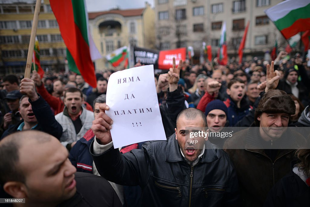 A protester holds a note reading 'We will not pay' during a protest in front of Bulgarian Parliament building in Sofia on February 17, 2013. The protesters threw rocks, firecrackers, bottles, eggs and tomatoes at the police line manning the headquarters of Czech power producer CEZ and the president's office to protest against sky-high January electricity bills in the EU's poorest country, as the government drags its feet on liberalising the energy market.