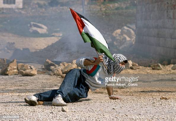 A protester holds a Palestinian flag as he ducks down near an Israeli building in Ramallah during the First Intifada During the conflict Palestinian...