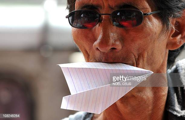 A protester holds a paper plane during a picket in front of the Philippine Airlines office in Manila on August 5 to show their support to Filipino...