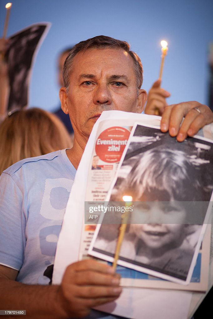 A protester holds a photo of Ionut Anghel, a four year-old who was killed by five stray dogs earlier this week, during a rally organized to demand that the authorities come up with a solution to the stray dog population in Bucharest, on September 6, 2013.