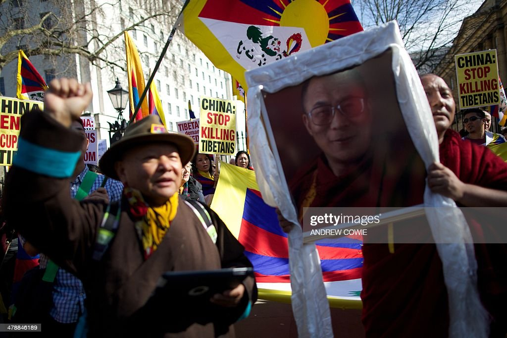 A protester holds a picture of the Dalai Lama as others wave the Tibetan flag during a Free Tibet rally outside Downing Street in London on March 15, 2014. The annual march marks the anniversary of Tibetans' uprising against Chinese rule on March 10, 1959.