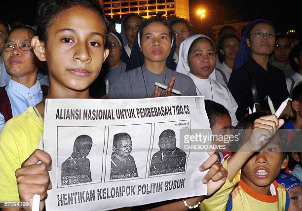 A protester holds a picture of three Christians sentenced to death during a demonstration against their planned execution in Jakarta 09 April 2006...