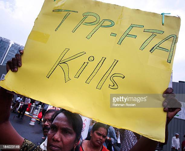 A protester holds a placard against the Trans Pacific Partnership Agreement during a protest outside the Global Entrepreneurship Summit on October 11...