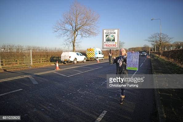 A protester holds a placard as workmen begin the construction of the shale gas fracking site near Westby on January 5 2017 in Blackpool England...