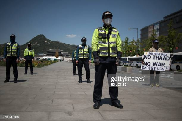 A protester holds a placard denouncing the THAAD antimissile defence system in central Seoul on April 26 2017 US troops began delivering a missile...