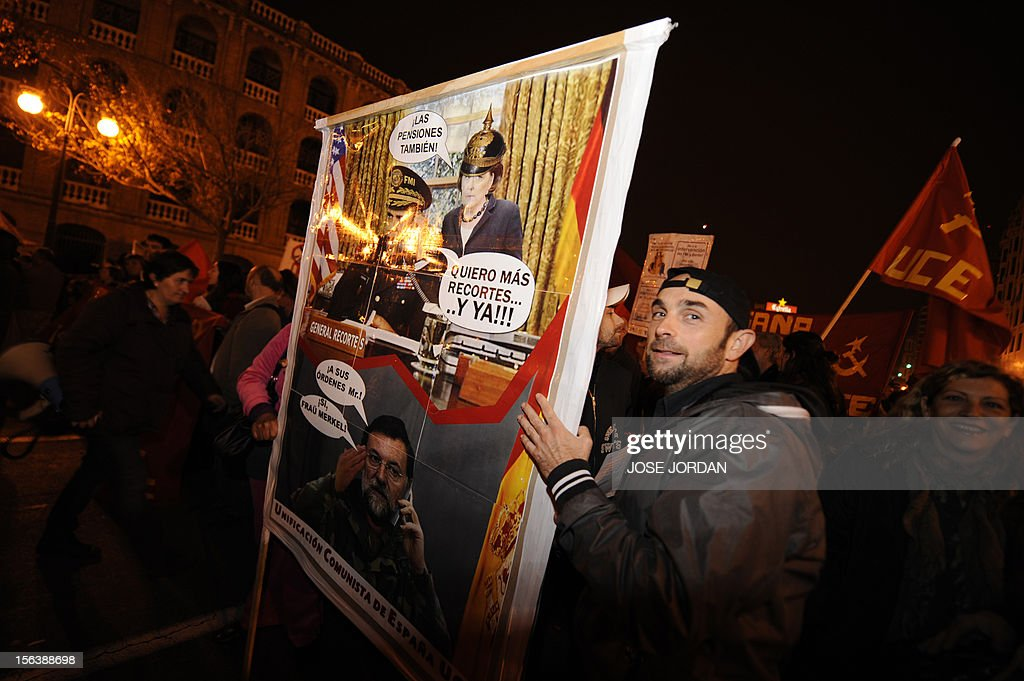 A protester holds a placard depicting German Chancellor Angela Merkel and Spanish Prime Minister Mariano Rajoy as protesters attend a demonstration during a general strike on November 14, 2012 in Valencia. The second general strike this year hit Spain with protesters marching in several cities against sweeping austerity measures and high unemployment, scenes echoed elsewhere in Europe. Spain, the eurozone's fourth-biggest economy, is suffering 25 percent unemployment, with the rate even higher amongst young people.