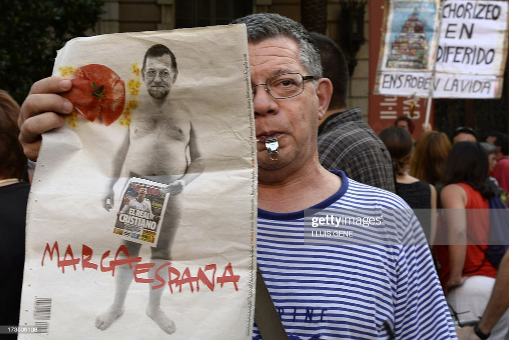 A protester holds a placard depicting Spanish Prime Minister Mariano Rajoy during a demonstration against corruption outside the People Party's headquarters in Barcelona on July 15, 2013. Spanish Prime Minister Mariano Rajoy faced calls today to resign or explain his ties to a slush fund scandal roiling the ruling Popular Party, whose jailed former treasurer appeared in court. The issue blew up again after the publication of friendly mobile text messages he purportedly sent to the disgraced treasurer at the heart of the affair.