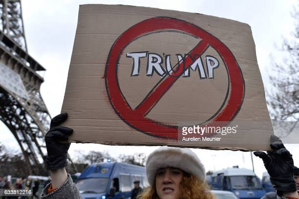 A protester holds a placard during a demonstration against Donald Trump as she walks by the Eiffel Tower on February 4 2017 in Paris France After US...