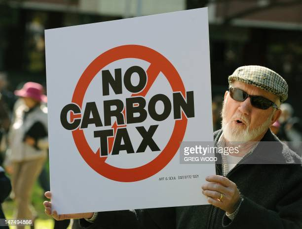 A protester holds a placard during a no carbon tax rally in Sydney on July 1 2012 Australia on July 1 introduced a controversial carbon tax in a bid...