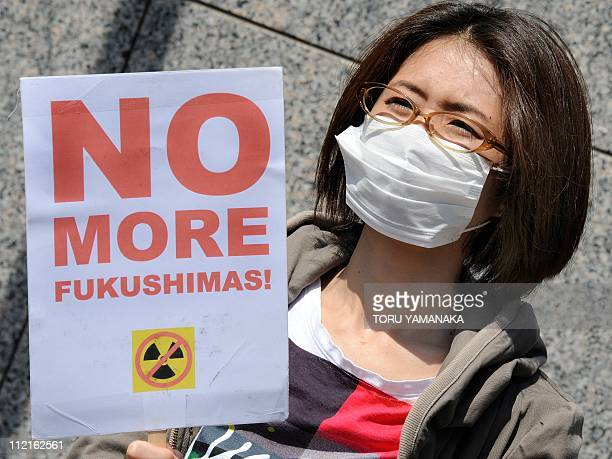 A protester holds a placard during a rally denouncing nuclear power plants in front of the headquarters of Tokyo Electric Power Company in Tokyo on...