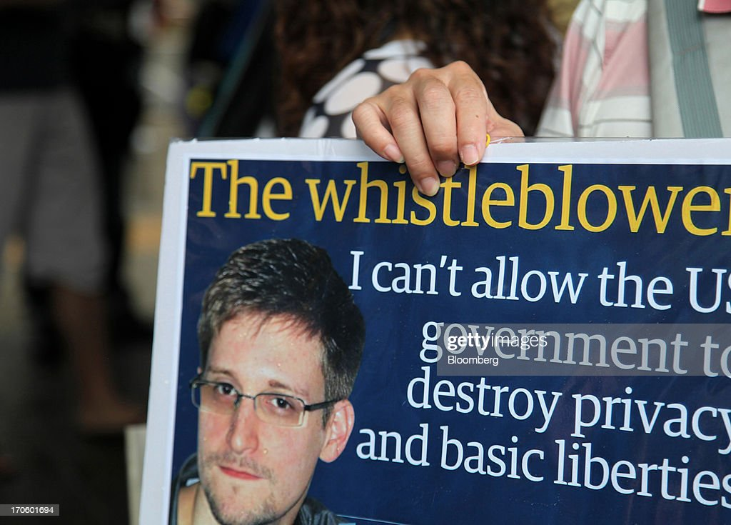 A protester holds a placard during a rally in support of Edward Snowden, the former National Security Agency contractor, in Hong Kong, China, on Saturday, June 15, 2013. Protesters marched to Hong Kongs government headquarters demanding their leaders protect Edward Snowden, who fled to the city after exposing a U.S. surveillance program. Photographer: Luke Casey/Bloomberg via Getty Images