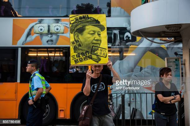 A protester holds a placard of Chinese President Xi Jinping during a march in Hong Kong on August 20 to protest the jailing of Joshua Wong Nathan Law...