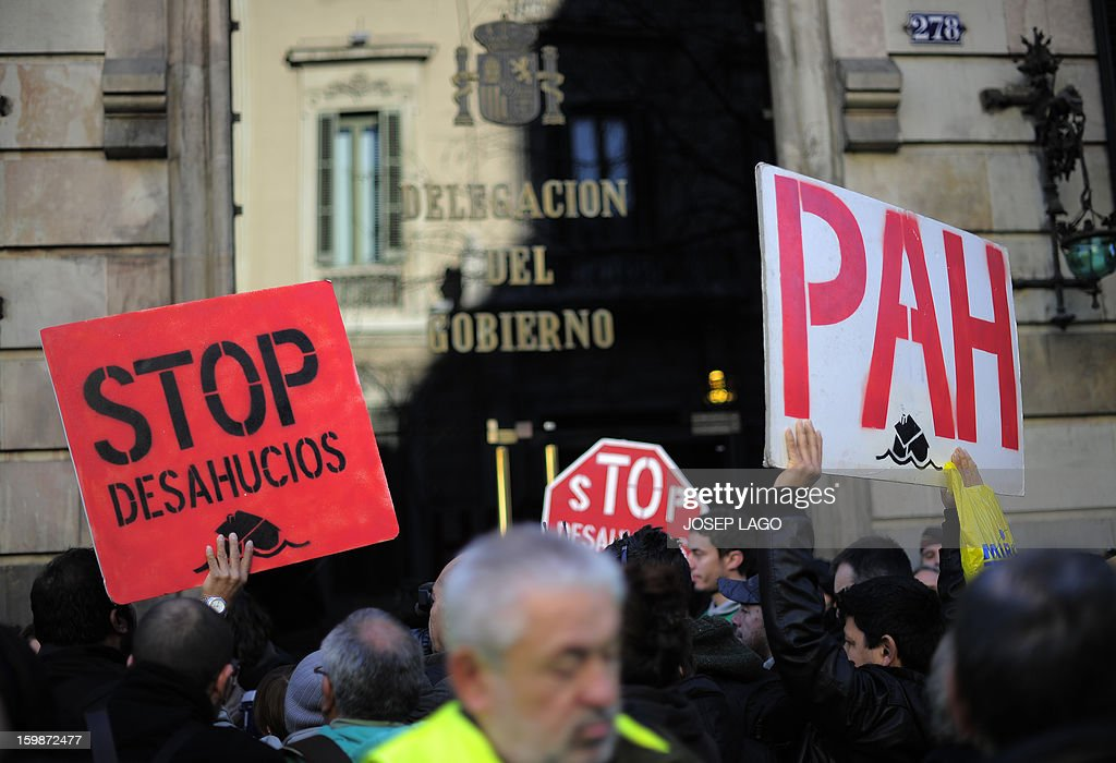 A protester holds a placard of the PAH (the Platform of People Affected by Mortgage) during a demonstration organized by anti-eviction activists and members of the 'iaioflautas' organization to protest against evictions outside the Spanish Government Delegation headquarters in Barcelona on January 22, 2013. The palcards read: 'Stop evictions'