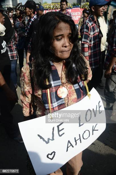 A protester holds a placard outside the Indonesian High Court building in Jakarta on May 12 to demand the release of Jakarta's governor Basuki...