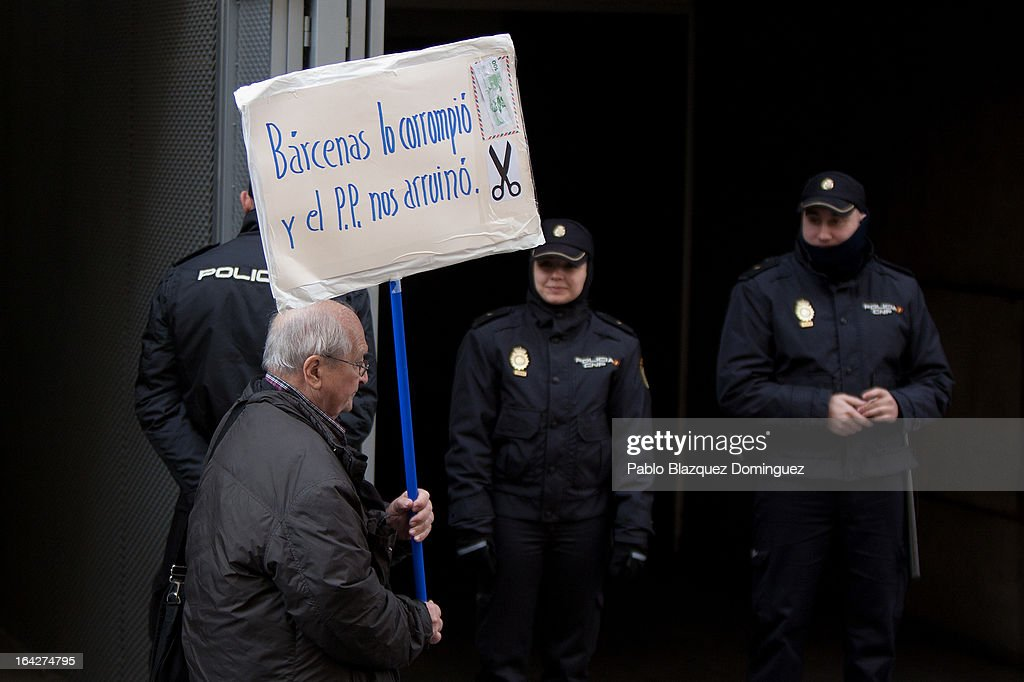 A protester holds a placard reading 'Barcenas corrupted it, and the Popular Party ruined us' outside the Madrid National Court while Luis Barcenas appears in court on March 22, 2013 in Madrid, Spain. Barcenas is being investigated for possible fraud offenses while he was treasurer of the Popular Party.