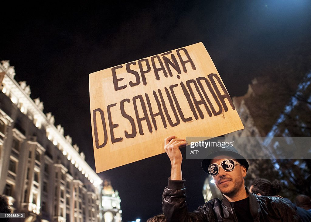 A protester holds a placard reading 'Evicted Spain' as he attends a demonstration during a general strike on November 14, 2012 in Madrid. The second general strike this year hit Spain with protesters marching in several cities against sweeping austerity measures and high unemployment, scenes echoed elsewhere in Europe. Spain, the eurozone's fourth-biggest economy, is suffering 25 percent unemployment, with the rate even higher amongst young people.