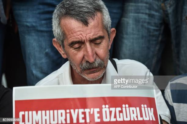 A protester holds a placard reading 'Freedom to Cumhuriyet' during a demonstration in Istanbul on July 28 2017 after a Turkish court ordered the...