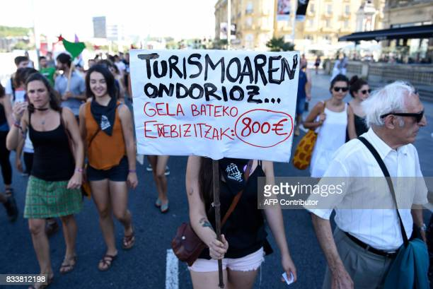 A protester holds a placard reading in Basque 'Because of tourism One rooms flat equal 800 euros' during a demonstration against mass tourism in the...