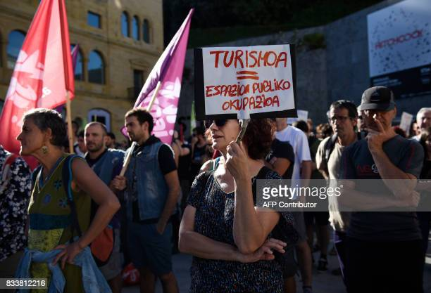A protester holds a placard reading in Basque 'Tourism equal Occupation of public space' during a demonstration against mass tourism in the Spanish...