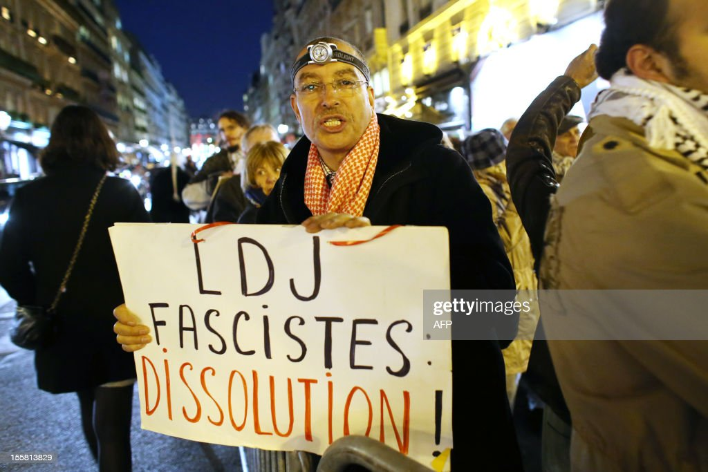 A protester holds a placard reading 'LDJ - fascists - dissolution' during a demonstration with about 120 members of the 'Indigenous of the Republic's Party' (PIR), on November 8, 2012 in front of France's Justice Ministry in Paris, to claim the dissolution of the Jewish Defence League (LDJ), as they accuse this jewish organisation of far-right attacks on pro-Palestinian supporters. On October 25, the LDJ uploaded on Youtube website a video showing PIR's spokeswoman Houria Bouteldja and pro-Palestinian militants Olivia Zemor and Jacob Cohen, sprayed with red paint after being assaulted by LDJ members. AFP PHOTO / THOMAS SAMSON