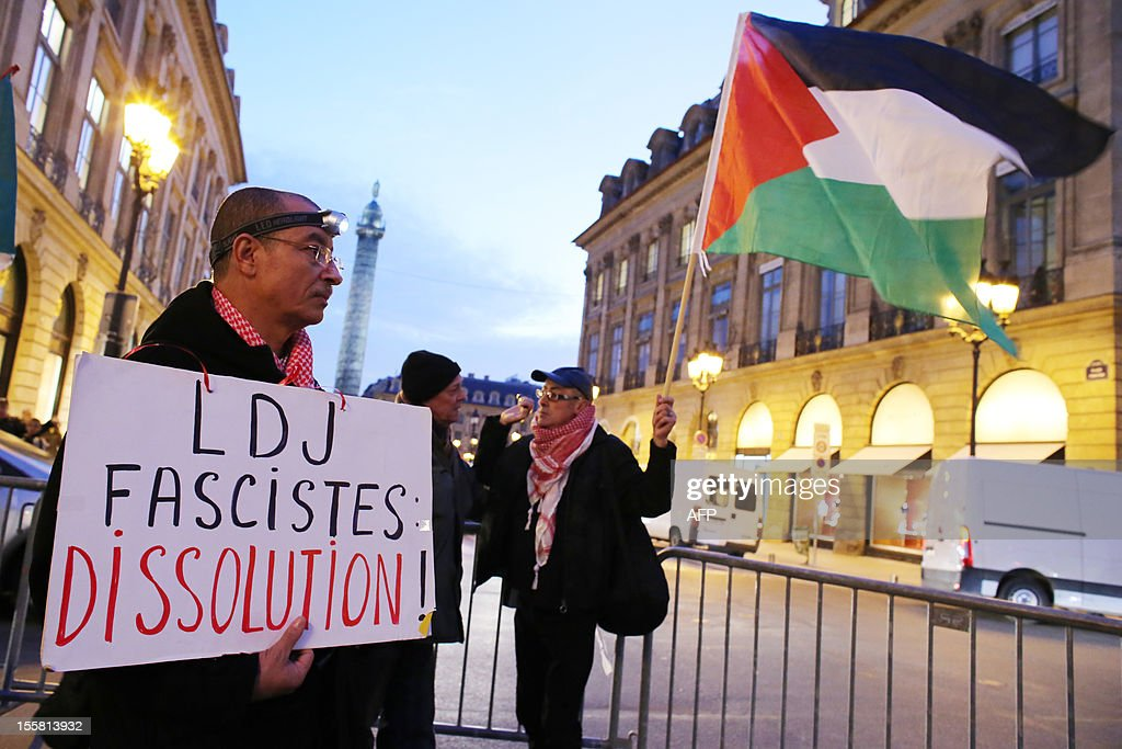 A protester holds a placard reading 'LDJ - fascists - dissolution' in front of a protester holding a Palestinian flag during a demonstration with about 120 members of the 'Indigenous of the Republic's Party' (PIR), on November 8, 2012 in front of France's Justice Ministry in Paris, to claim the dissolution of the Jewish Defence League (LDJ), as they accuse this jewish organisation of far-right attacks on pro-Palestinian supporters. On October 25, the LDJ uploaded on Youtube website a video showing PIR's spokeswoman Houria Bouteldja and pro-Palestinian militants Olivia Zemor and Jacob Cohen, sprayed with red paint after being assaulted by LDJ members.