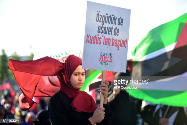 A protester holds a placard reading 'Liberty and captivity starts in Jerusalem' as other protesters wave Turkish and Palestinian flags during a...