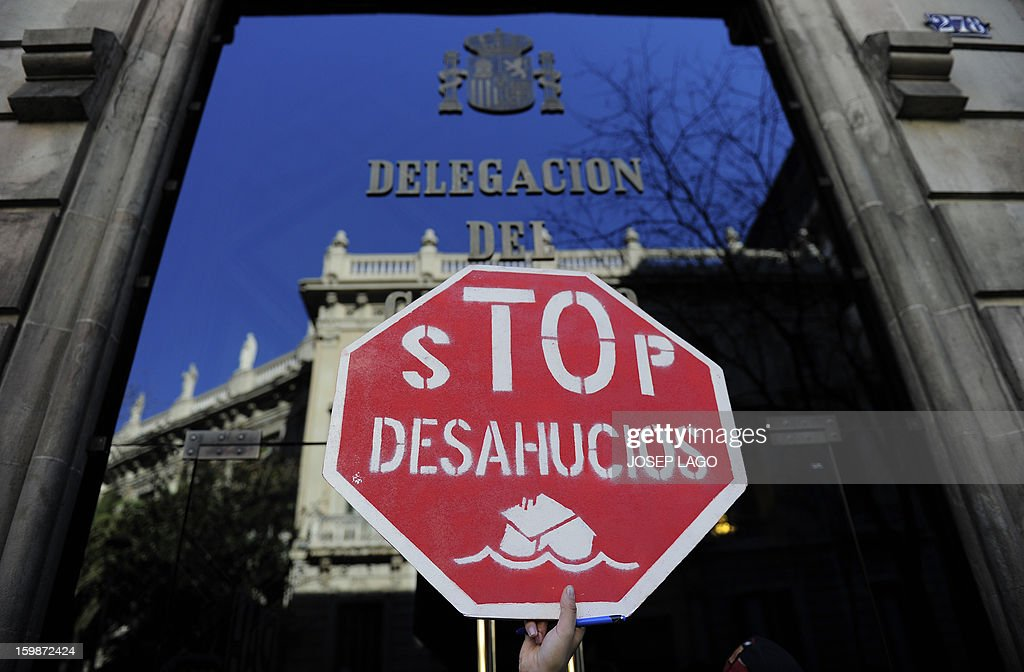 A protester holds a placard reading 'Stop evictions' during a demonstration organized by anti-eviction activists and members of the 'iaioflautas' organization to protest against evictions outside the Spanish Government Delegation headquarters in Barcelona on January 22, 2013.