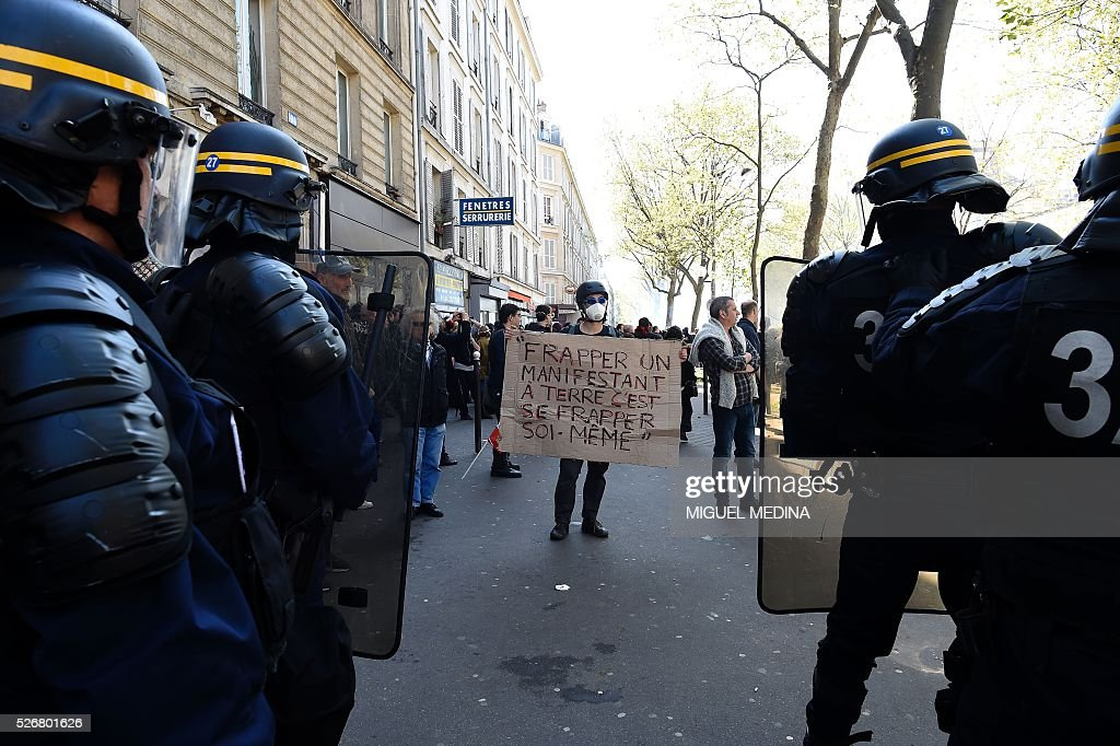 A protester holds a placard reading 'To hit a protester on the ground is to hit yourself' as he faces riot police during a traditional May Day demonstration on May 1, 2016, in Paris.